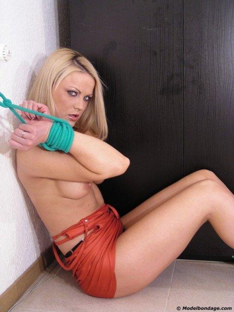Развратная связанная блондинка в бондаже позирует с голой писькой