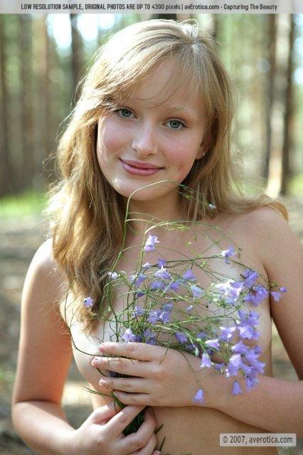 Сексуальная девочка позирует голой в лесу лаская гладкую киску