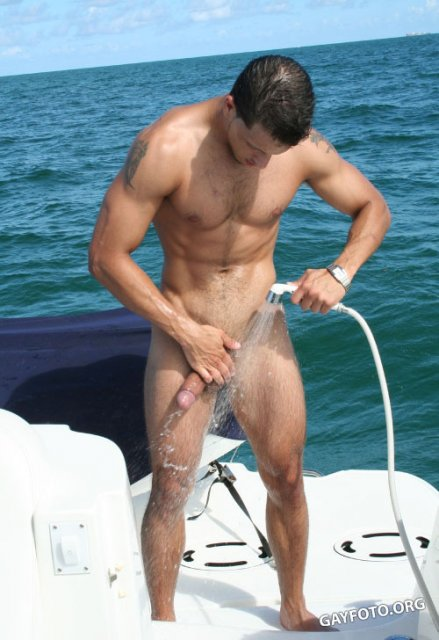 Накачанный голый парень с длинным членом позирует на природе