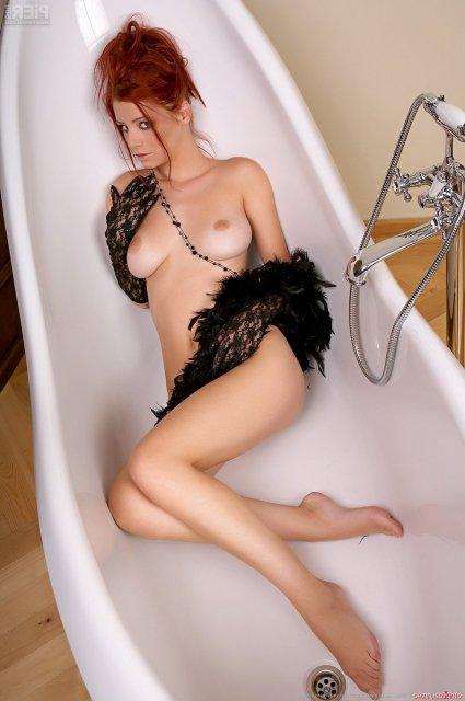 Обнажённая рыжая телка с тёмными сосками позирует в ванной