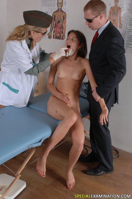Опытный доктор в кабинете изучает голую девицу